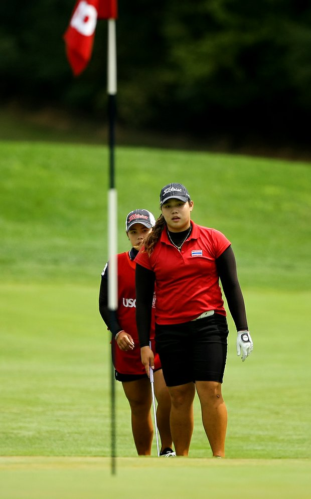 Ariya Jutanugarn, right, with her sister Moriya, behind, look over a shot during the Round of 32 at the 112th U. S. Women's Amateur Championship.