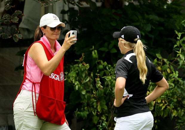 Texas A&M head coach Trelle McCombs still wearing her caddie bib interviews her collegiete player, Sarah Beth Davis, during the Round of 32 at the 112th U. S. Women's Amateur Championship.