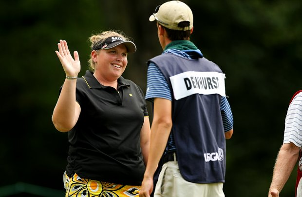 Ashlee Dewhurst of Australia high fives her caddie after defeating fellow Australian Breanna Elliott during the Round of 32 at the 112th U. S. Women's Amateur Championship.