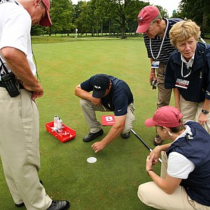 USGA staff members, Mark Hill, left, Bob Brame, top right, Martha Lang, and Shannon Rouillard, help The Country Club assistant superintendent Adam Farrell, center, repair the hole at No. 8  during the Round of 16 at the 112th U. S. Women's Amateur Championship.