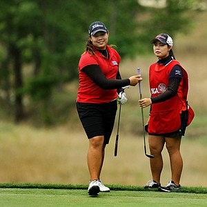 Ariya Jutanugarn, left, and her sister, Moriya, right, who was knocked out in the Round of 64 discuss club choice at No. 16 during the Round of 16 at the 112th U. S. Women's Amateur Championship. Moriya was knocked out in the Round of 64 and decided to caddie for her sister.
