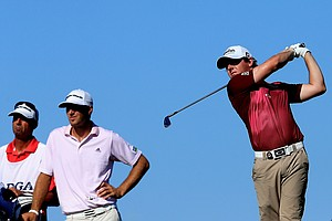 Rory McIlroy of Northern Ireland hits off the 14th tee as Dustin Johnson of the United States looks on during Round One of the 94th PGA Championship at the Ocean Course on August 9, 2012 in Kiawah Island, South Carolina.