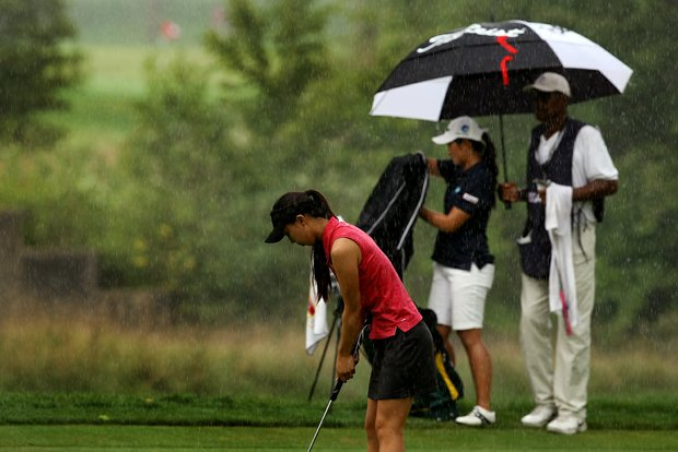 Nicole Zhang prepares to putt as Su-Hyun Oh tries to keep dry during the quarterfinals at the 112th U. S. Women's Amateur Championship. Start of play was delayed due to rain on Friday.