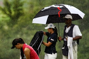 Nicole Zhang prepares to putt as Su-Hyun Oh tries to keep dry during the quarterfinals at the 112th U. S. Women's Amateur Championship. Start of play was delayed due to rain.