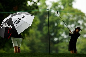 Su-Hyun Oh keeps dry under an umbrella as Nicole Zhang prepares to hit as the rain comes down at No. 11 during the quarterfinals at the 112th U. S. Women's Amateur Championship at The Country Club in Cleveland. The start of play was delayed due to rain.