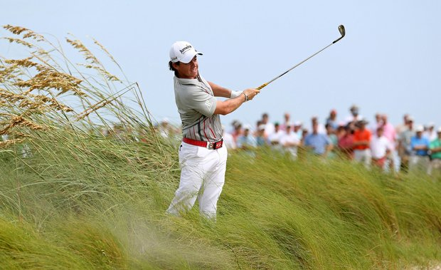 Rory McIlroy hits a shot on the seventh hole as heavy winds blow tall grass during Round Two of the 94th PGA Championship at the Ocean Course on August 10, 2012 in Kiawah Island, S.C.