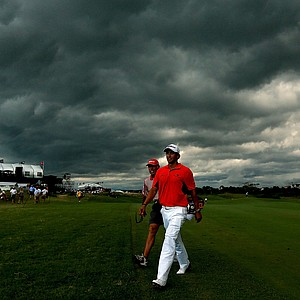 Adam Scott walks off the course under dark clouds as play is suspended due to a weather warning during Round Three of the 94th PGA Championship at the Ocean Course on August 11, 2012 in Kiawah Island, South Carolina.