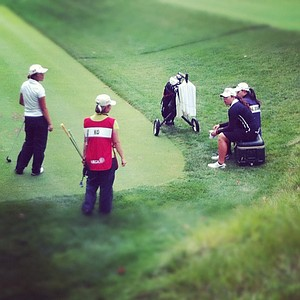 Ariya Jutanugarn and her sister Moriya sit on a cooler while waiting for Lydia Ko to hit during the semifinals at the 112th U. S. Women's Amateur Championship.