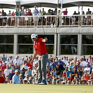 Rory McIlroy holds his putter up in celebration as he putts on the 18th green at the PGA Championship.