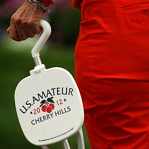 A spectator carries a seat around the course during the 112th U. S. Amateur Championship at Cherry Hills Country Club in Colorado.