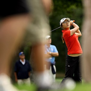 Lydia Ko is framed by the legs of spectators as she hits a shot during the second round of the finals at the 112th U. S. Women's Amateur Championship.