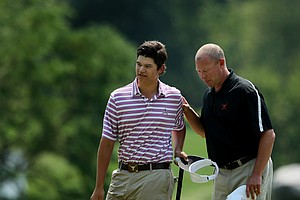 Beau Hossler of Mission Viejo, Calif., with his caddie William Schellenberg at No. 18 during the 112th U. S. Amateur Championship.