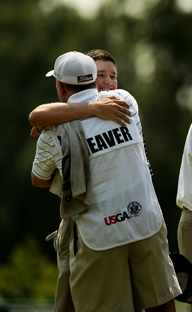 Michael Weaver gets a hug from his father/caddie Bill during the quarterfinals of the 112th U. S. Amateur Championship at Cherry Hills Country Club in Colorado. Weaver will face Justin Thomas in the semifinals.