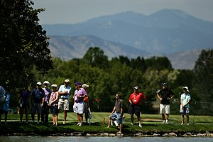 Spectators line the water near the second green and No. 3 tee to watch the last group hit their tee shots at No. 18 during the semifinals of the 112th U. S. Amateur Championship at Cherry Hills Country Club in Cherry Hills Village, Colo.