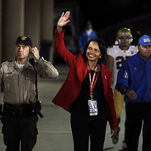 Honorary captain and former Secretary of State Condoleezza Rice waves to the crowd against the Stanford Cardinal she enters the stadium for the Stanford Cardinal game against the UCLA Bruins at Stanford Stadium on October 1, 2011 in Stanford, California.