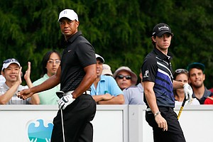 Rory McIlroy and Tiger Woods look on from the tee box on the 11th hole during the First Round of The Barclays.