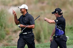 Tiger Woods and Rory McIlroy share a laugh as they walk up the 18th hole fairway during the First Round of The Barclays.