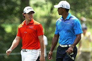 Rory McIlroy talks with Tiger Woods as they walk up the fairway on the second hole during the second round of The Barclays.