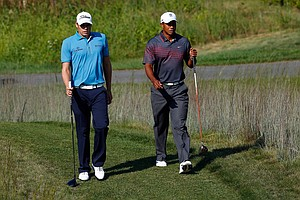 Nick Watney and Tiger Woods talk as they walk towards the 13th green during the first round of the Deutsche Bank Championship at TPC Boston.