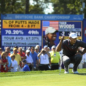 Tiger Woods studies his putt on the 15th hole during the first round of the Deutsche Bank Championship at TPC Boston.