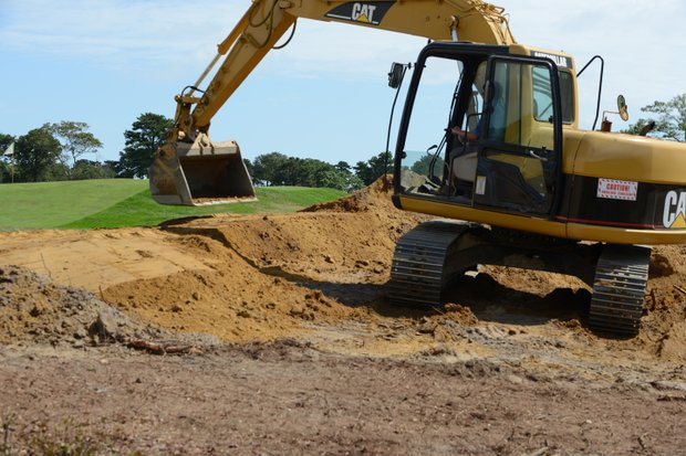 Initially the face of the bunker is created by heavy equipment, then the shapers come in and finish off the bunker by hand.