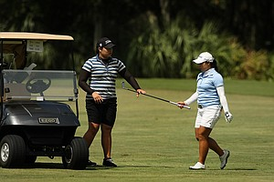 Moriya Jutanugarn hands her club to her sister Ariya during the first day of LPGA Qualifying School at LPGA International. Jutanugarn posted a 69.