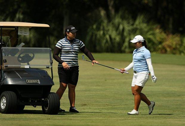 Moriya Jutanugarn hands her club to her sister Ariya during the first day of LPGA Qualifying School at LPGA International. Jutanugarn posted a 69.