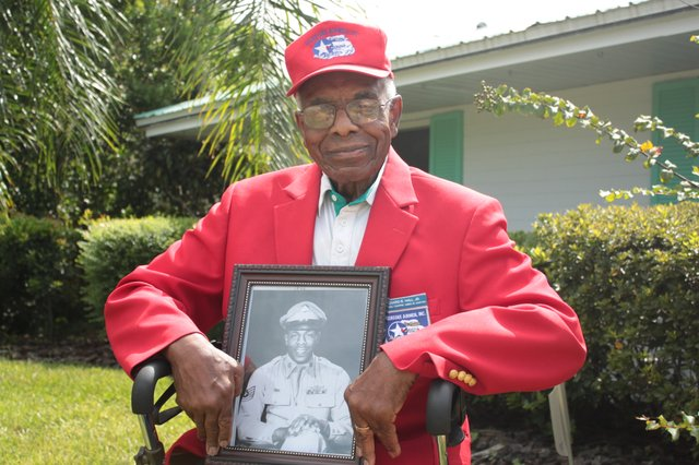 Richard Hall Jr., 88, sits outside his Maitland home and holds a photo taken of him in his days as a Tuskegee Airmen pilot fighting in Europe.