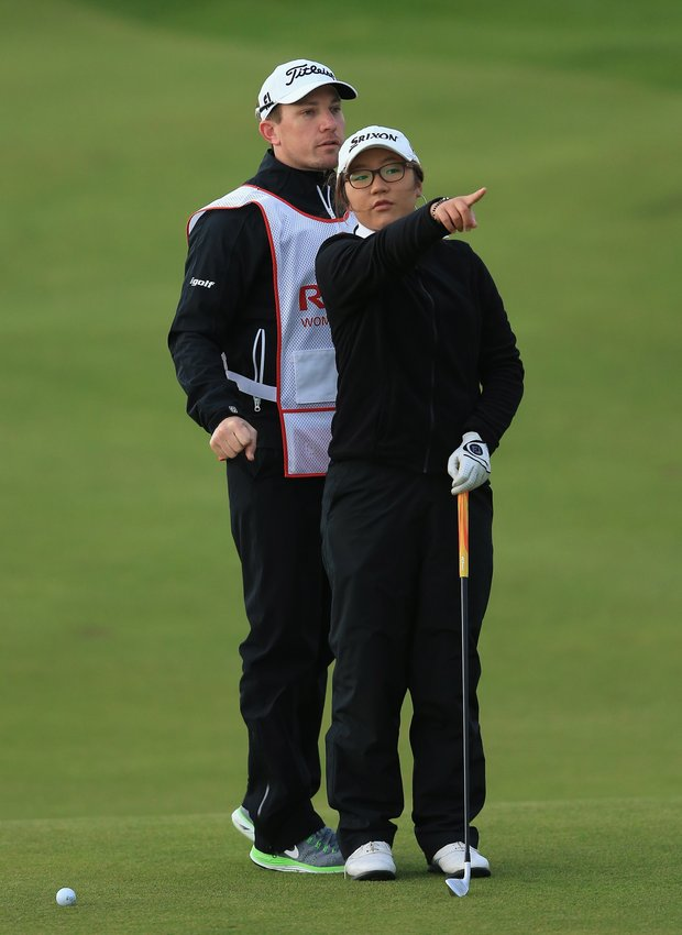 Lydia Ko (Amateur) of New Zealand lines up her 2nd shot on the 11th hole with her caddie during the first round of the Ricoh Women's British Open.