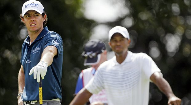 Rory McIlroy, left, waits to tee off on the second hole as Tiger Woods watches during first round of play in the Tour Championship golf tournament in Atlanta on Thursday, Sept. 20, 2012.