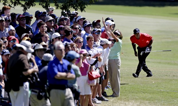 Tiger Woods, right, ducks to watch the flight of his ball after hitting out of the rough off the fairway of the second hole during the final round of the Tour Championship golf tournament on Sunday, Sept. 23, 2012, in Atlanta. (AP Photo/David Goldman)