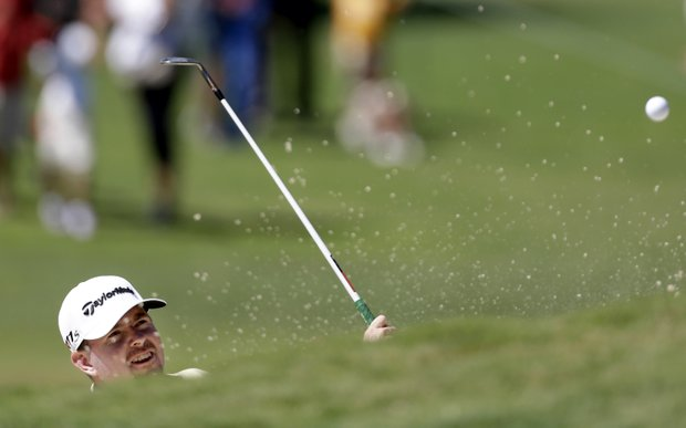 Robert Garrigus hits out of the sand trap on the second hole during the final round of the Tour Championship golf tournament on Sunday, Sept. 23, 2012, in Atlanta. (AP Photo/David Goldman)