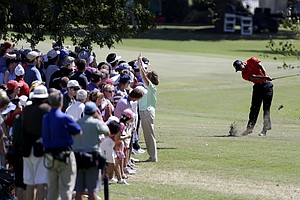 Tiger Woods hits out of the rough off the fairway of the second hole during the final round of the Tour Championship golf tournament Sunday, Sept. 23, 2012, in Atlanta. (AP Photo/David Goldman)