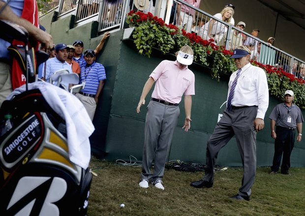 Brandt Snedeker, center, takes a drop alongside an official after hitting his tee shot into the stands on the 18th hole during the final round of the Tour Championship golf tournament, Sunday, Sept. 23, 2012, in Atlanta. (AP Photo/David Goldman)
