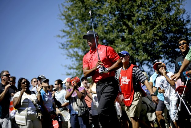 Tiger Woods is cheered by the crowds after hitting out of the rough off the fairway of the fourth hole during the final round of the Tour Championship golf tournament Sunday, Sept. 23, 2012, in Atlanta. (AP Photo/David Goldman)