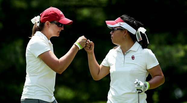 Oklahoma head coach Veronique Drouin-Luttrell (left) fist bumps junior Chirapat Jao-Javanil.