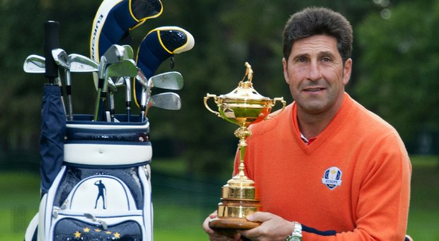 Jose Maria Olazabal poses with the Ryder Cup, as well as the stand bag with Seve Ballesteros' image on it.