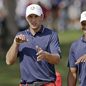 USA's Dustin Johnson, left, talks to Tiger Woods during a practice round at the Ryder Cup PGA golf tournament Wednesday, Sept. 26, 2012, at the Medinah Country Club in Medinah, Ill.