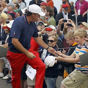USA's Phil Mickelson hands out pins as he walks off the third tee at the Ryder Cup PGA golf tournament Wednesday, Sept. 26, 2012, at the Medinah Country Club in Medinah, Ill.