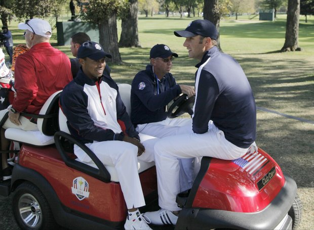 USA's Tiger Woods, left, and Dustin Johnson gets a ride to the course for a practice round at the Ryder Cup Thursday, Sept. 27, 2012, at the Medinah Country Club in Medinah, Ill.