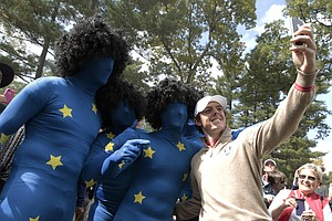 Europe's Rory McIlroy takes his pictures with some fans during a practice round at the Ryder Cup Thursday, Sept. 27, 2012, at the Medinah Country Club in Medinah, Ill.