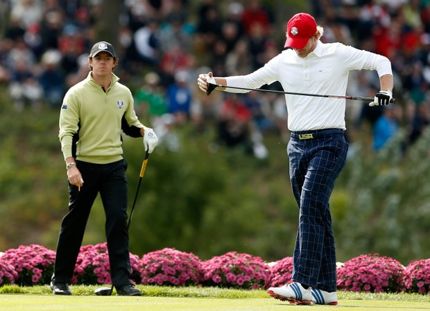 Brandt Snedeker of the USA reacts after his tee shot on the 18th hole as Rory McIlroy of Europe looks on during the morning foursome matches.