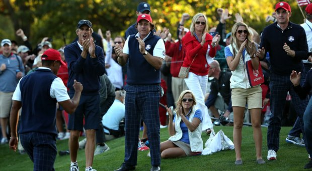 Tiger Woods of the USA passes Phil Mickelson and and Keegan Bradley after making birdie on the 16th hole.