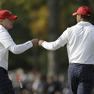 USA's Tiger Woods, right, and Steve Stricker react after saving par on the seventh hole during a foursomes match at the Ryder Cup Friday, Sept. 28, 2012, at the Medinah Country Club in Medinah, Ill.