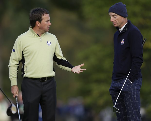 Europe's Graeme McDowell, left, and USA's Jim Furyk talk about getting relief during a foursomes match at the Ryder Cup Friday, Sept. 28, 2012, at the Medinah Country Club in Medinah, Ill.