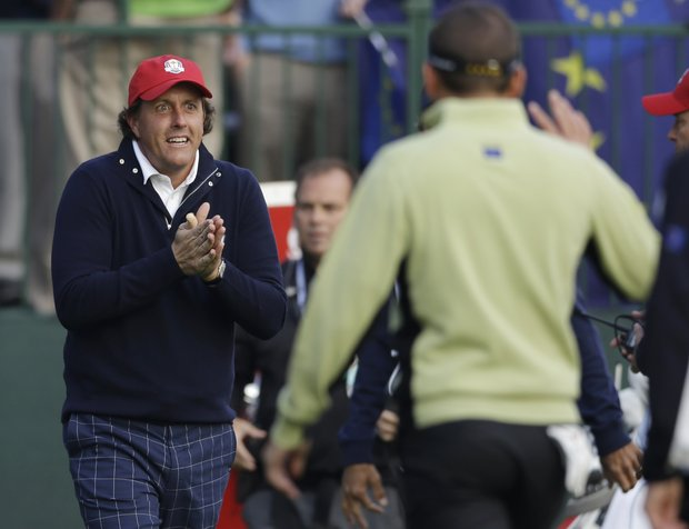 USA's Phil Mickelson warms his hands as he greets Europe's Sergio Garcia on the first tee during a foursomes match at the Ryder Cup PGA golf tournament Friday, Sept. 28, 2012, at the Medinah Country Club in Medinah, Ill.