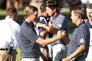 Webb Simpson, left, is greeted by USA team captain Davis Love III on the 14th green after the team of Simpson/Watson defeated the team of Rose/Molinari 5 and 4 during their afternoon four-ball match at the 39th Ryder Cup at Medinah Country Club on September 29, 2012 in Medinah, Illinois.