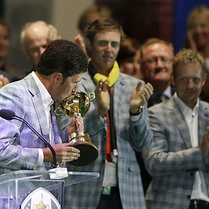 Europe's Nicolas Colsaerts and Luke Donald watch as team captain Jose Maria Olazabal kisses the trophy at the closing ceremony at the Ryder Cup PGA golf tournament Sunday, Sept. 30, 2012, at the Medinah Country Club in Medinah, Ill.