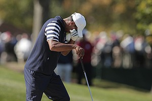 USA's Tiger Woods wipes his eyes after hitting out of a bunker on the second hole during a singles match at the Ryder Cup PGA golf tournament Sunday, Sept. 30, 2012, at the Medinah Country Club in Medinah, Ill.