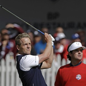 USA's Bubba Watson, right, watches as Europe's Luke Donald hits a shot during a singles match at the Ryder Cup PGA golf tournament Sunday, Sept. 30, 2012, at the Medinah Country Club in Medinah, Ill.